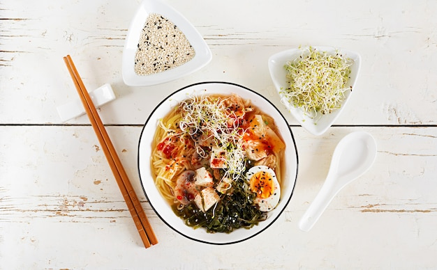 Miso noodles with cabbage kimchi, seaweed, egg, mushrooms and cheese tofu in bowl on white wooden table