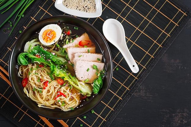 Мисо лапша с яйцом, свининой и пак чой капустой в миске на темном столе