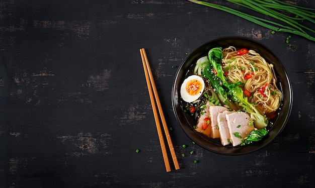Miso noodles with egg, pork and pak choi cabbage in bowl on dark table