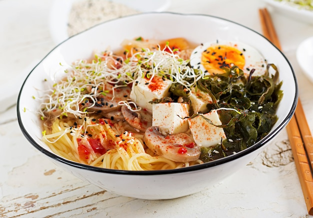 Miso ramen asian noodles with cabbage kimchi, seaweed, egg, mushrooms and cheese tofu in bowl on white wooden table. korean cuisine.