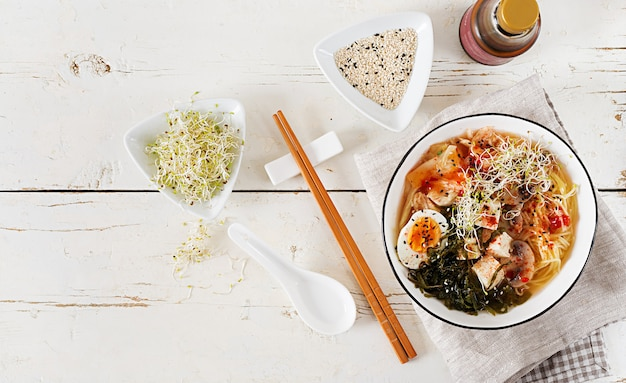 Miso ramen asian noodles with cabbage kimchi, seaweed, egg, mushrooms and cheese tofu in bowl on white wooden table.