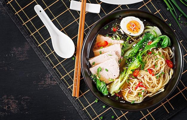 어두운 테이블에 그릇에 계란, 돼지 고기, 박 최 양배추와 미소라면 아시아 국수. 일본 요리. 평면도. 평평하다