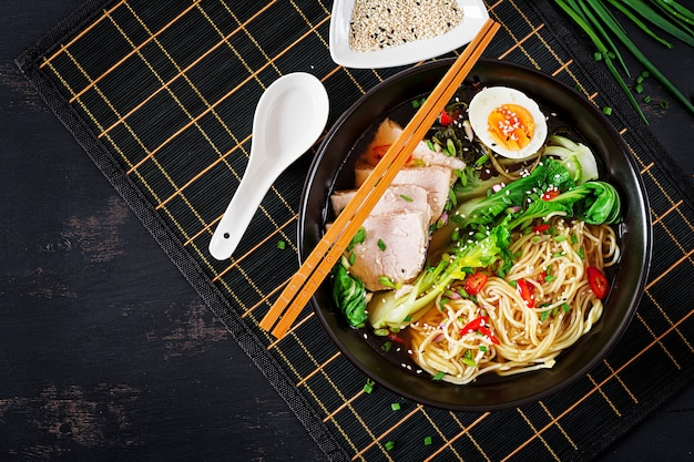 Miso ramen asian noodles with egg, pork and pak choi cabbage in bowl. japanese cuisine. top view. flat lay