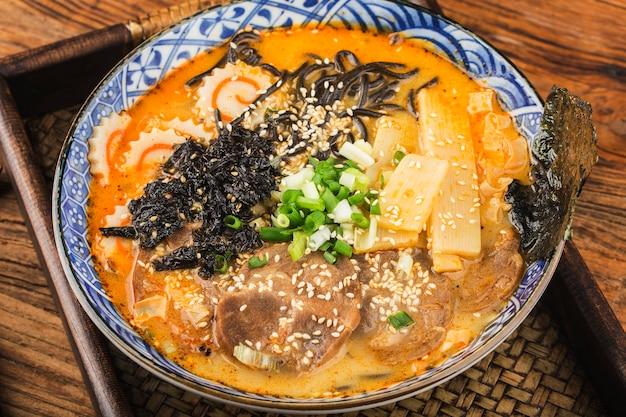 오징어 소스를 곁들인 튀긴 국수를 곁들인 미소 라멘 아시아 국수