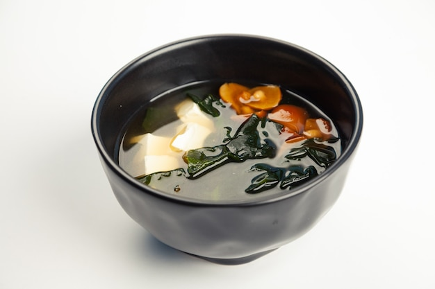 Miso soup in a black carriage.