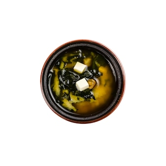 Miso soup in a  black cup isolated on white