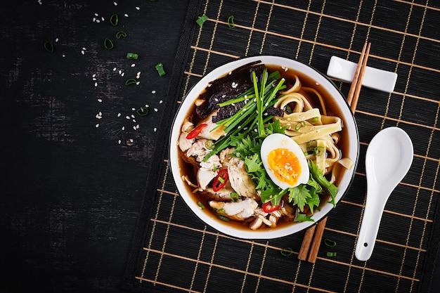 Мисо суп. японский суп рамэн с курицей, яйцом, нори и ниппосиникой на темном фоне. вид сверху, плоская планировка
