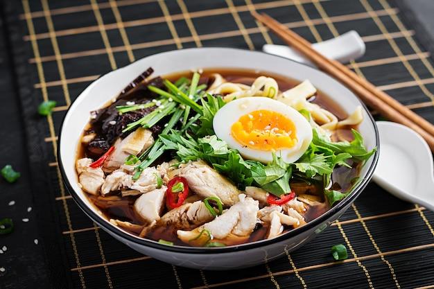 Мисо суп. японский суп рамэн с курицей, яйцом, нори и ниппосиникой на темном фоне.