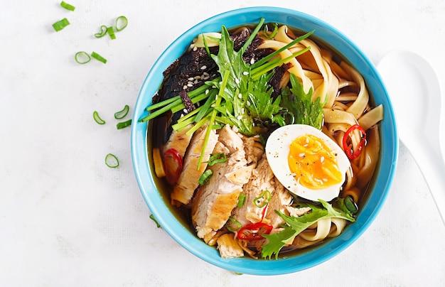Мисо суп. японский суп рамэн с курицей, яйцом, нори и ниппосиникой на светлом фоне. вид сверху, плоская планировка