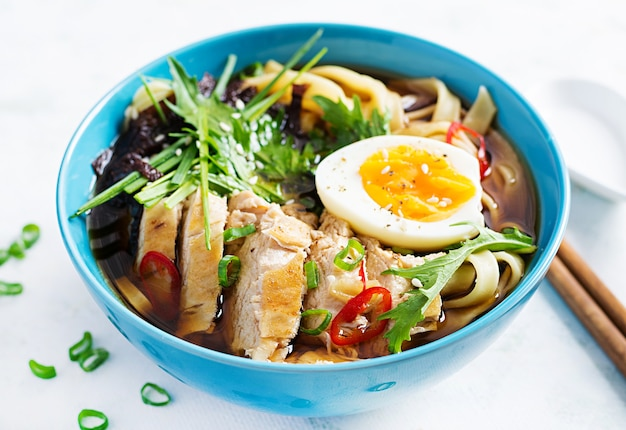 Miso soup. japanese ramen soup with chicken, egg, nori and nipposinica on light background.