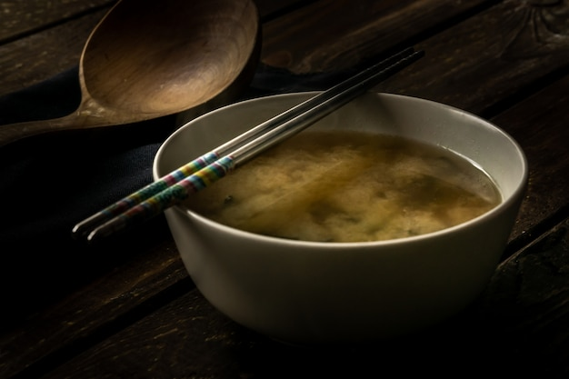 Miso soup in a white bowl with chopsticks