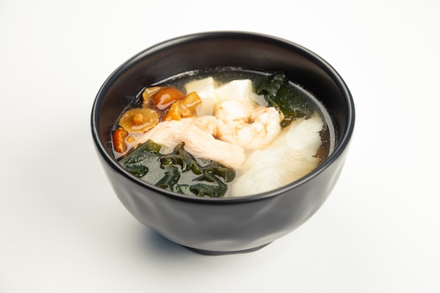Miso soup with seafood in a black karelka.
