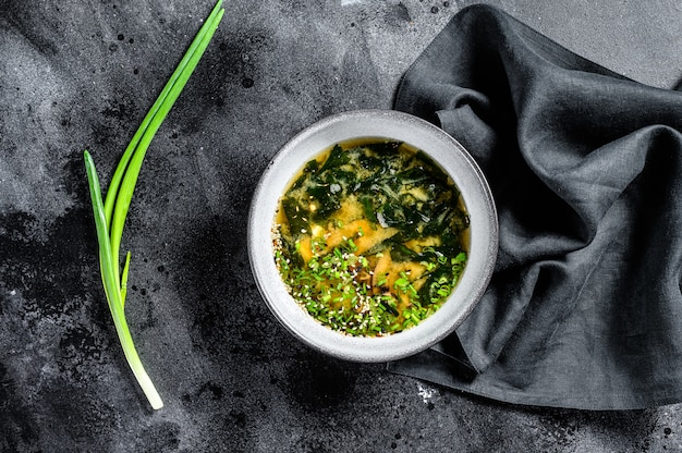Miso soup with tofu and seaweed. black background. top view
