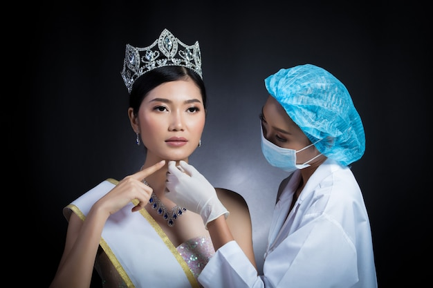 Miss beauty queen pageant contest with diamond crown sash is checked up by beautician doctor