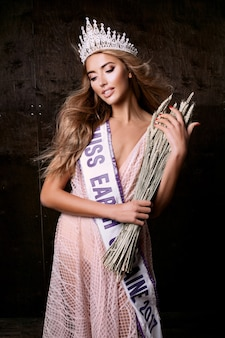 小麦の冠、リボン、小穂を身に着けているミスアースの女性。ファッションコンテスト、美しいモデルのポーズ