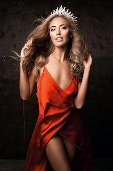 長いシルクの赤いドレスと王冠を身に着けているミスユニバース。ナチュラルメイク、巻き毛のヘアスタイル