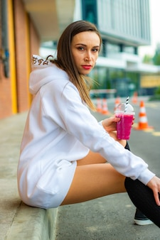 Miss in white sweatshirt and pink drink