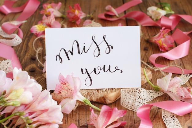 ピンクの花の間の木製のテーブルに手書きのカードを見逃すクローズアップ