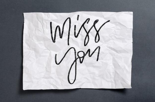 Miss you. handwritten text on white crumpled paper.