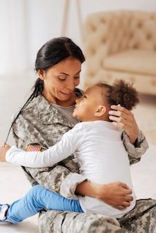 あなたがいなくて寂しかった。ゴージャスで優雅な若いお母さんと娘が床に座って抱きしめながらお互いをとても愛し合っていると語る