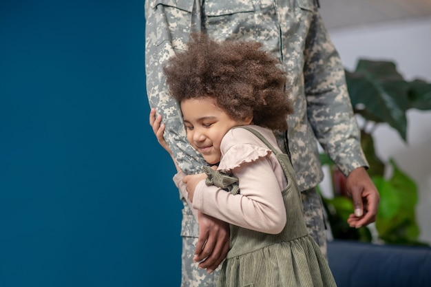 Misses dad. joyful little african american girl with closed eyes clutching hand of dad in military uniform standing at home