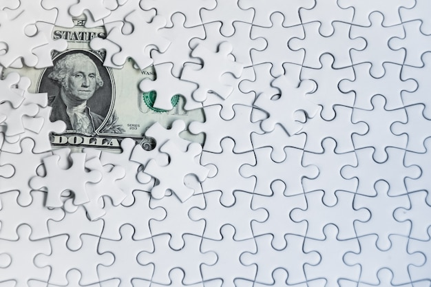 Missing jigsaw puzzle pieces on money dollar background.