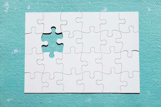 Missing piece of puzzle on blue textured backdrop