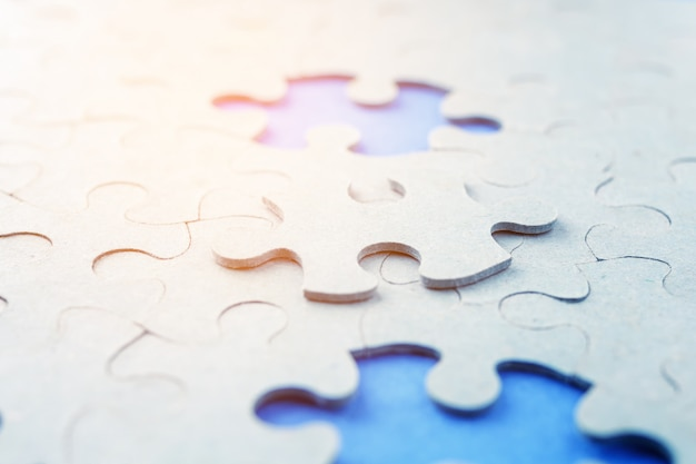 Missing puzzle pieces on a blue background.