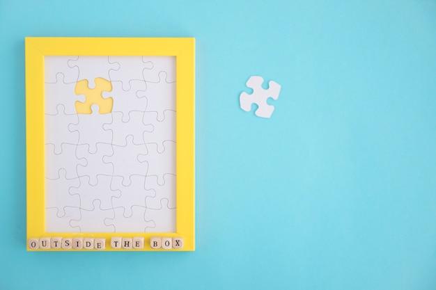 파란색 배경에 누락 된 흰색 직소 퍼즐 프레임