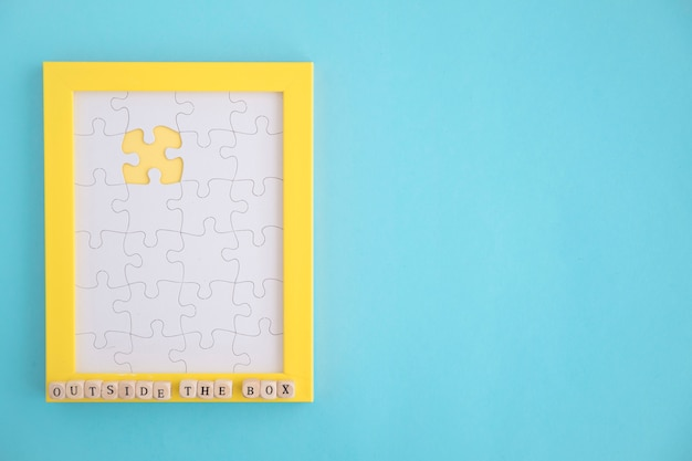 Missing white jigsaw puzzle yellow frame on blue background