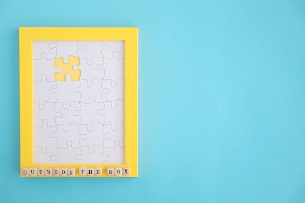 파란색 배경에 누락 된 흰색 직소 퍼즐 노란색 프레임