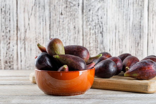 Mission figs in a bowl and on cutting board on a light wooden table. side view. free space for your text