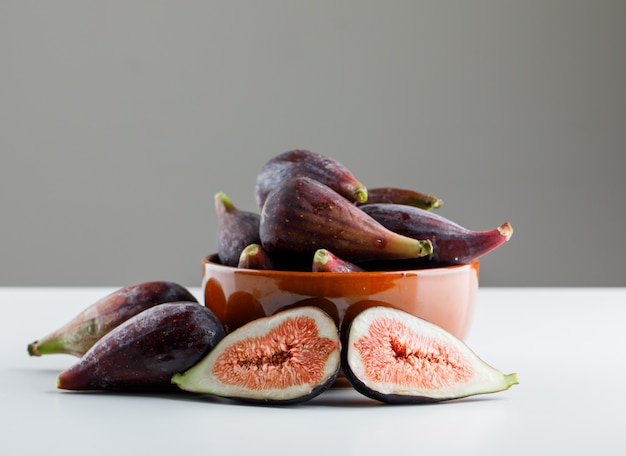 Mission figs in a bowl on a white table with dark background. side view. space for text