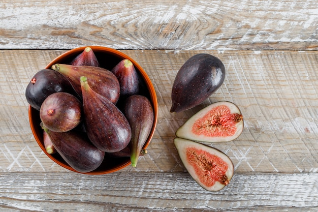 Mission figs and halves in a bowl and around top view on a wooden table