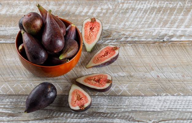Mission figs and halves in a bowl and around on a wooden table. high angle view. space for text