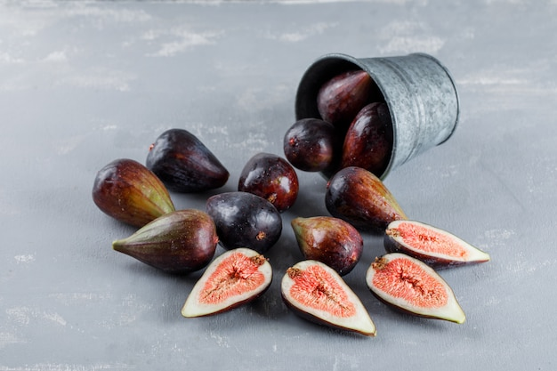 Mission figs and halves coming out of a bucket on a textured background. high angle view.