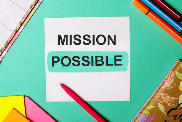 明るいステッカー、メモ帳、マーカーの近くのターコイズブルーの背景に書かれたミッションの可能性