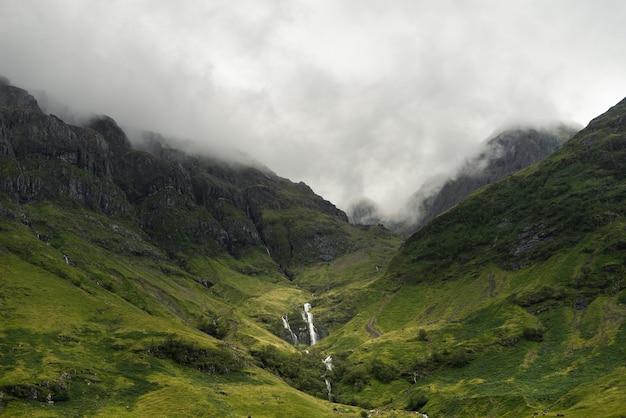昼間にスコットランドの山々に降り注ぐ霧