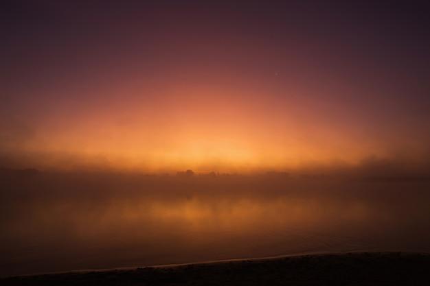 川の上の霧。自然の背景。朝日の出。美しい夏の霧の風景。湖の夕暮れ。霧深い夜明け。環境保護。非常に濃い霧。朝の夜明け。風光明媚なオレンジ色の夕日。