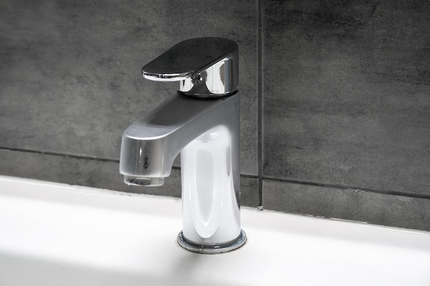 A misted chromed metal faucet for hot and cold water, located on a white sink against a gray concrete wall in a modern bathroom. selective focus. copy space