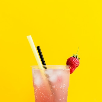 Misted glass of cocktail with strawberry and straws