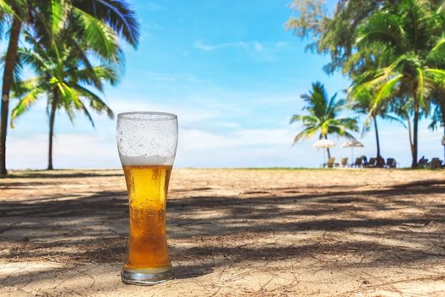 Запотевший стакан холодного пива на песке на фоне зеленых пальм, голубого неба и морского побережья. тропический остров. небесный восторг.