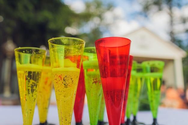 Запотевшие стаканы с разноцветными коктейлями с коктейльными трубками крупным планом