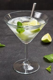 Misted wine glass with lime and ice. mint sprigs on table. black background. top view