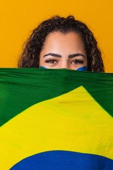 당신의 얼굴에 브라질 국기를 들고 신비한 흑인 여성 팬. 배경, 녹색, 파란색 및 노란색의 브라질 색상. 선거, 축구 또는 정치. 수직의