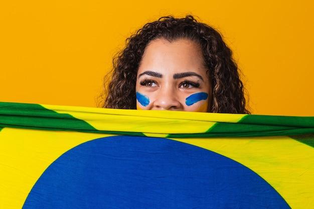 당신의 얼굴에 브라질 국기를 들고 신비한 흑인 여성 팬. 배경, 녹색, 파란색 및 노란색의 브라질 색상. 선거, 축구 또는 정치.