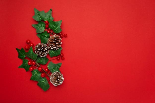 Омела и сосновые шишки на красном столе