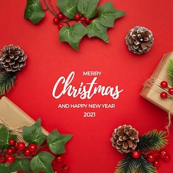 Омела, сосновые шишки и подарки на красном столе рождественское приветствие