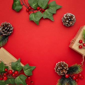 Mistletoe, pine cones and christmas gifts on red table