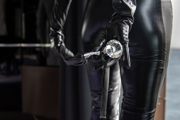 Mistress holds a whip behind her back
